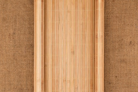 furled: Bamboo mat in the form of a manuscript on sackcloth, top view Stock Photo