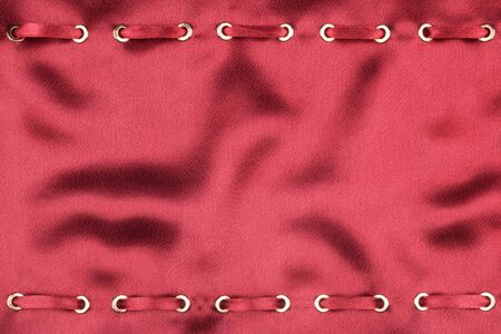 inserted: Fashionable beautiful background, red satin ribbon inserted in red satin fabric, with space for your creativity