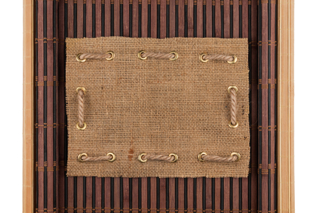 furled: Frame made of burlap lying on a bamboo mat in the form of manuscript, isolated on white background