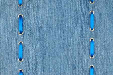 inserted: Blue satin ribbon inserted in the gold rings on denim, with space for your text Stock Photo