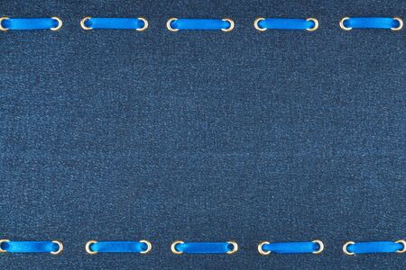 inserted: Fashionable beautiful background, blue satin ribbon inserted in denim fabric, with space for your creativity