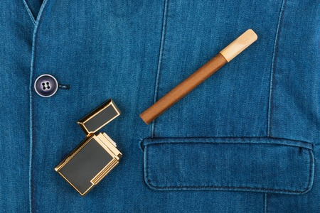 Cigar and lighter lying on a blue denim jacket, with space for your text Stock Photo