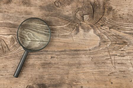 Magnifying glass lying on a wooden surface, top view Stock Photo