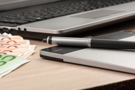 Working businessman desk,stylus, pen tablet, money, as the background, view from above Stock Photo