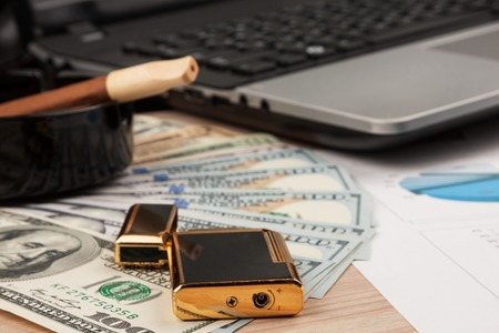 Working businessman desk, Lighter and laptop, cigar and money as the background