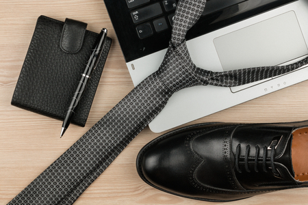 Fashion and business, notebook, shoes and tie on a wooden table as background, top view