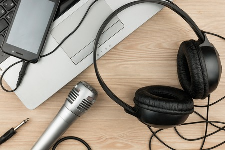 Laptop, microphone, headsets lies on a wooden table, background, top view Stock Photo