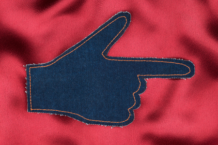 Hand in the shape a pointer made of denim jeans on red satin, with place for your text