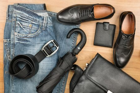 Classic black shoes, briefcase, jeans and umbrella on the wooden floor, can be used as background