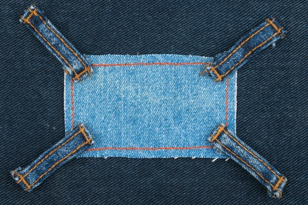 Frame made of denim with four straps of jeans, lies on the dark denim, view from above