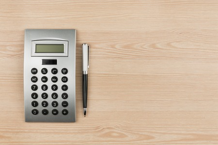 Close-up of luxury black pen and calculator on wooden desk, with space for your text