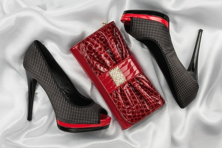 Red lacquer bag and shoes with toeless on a white crumpled fabric