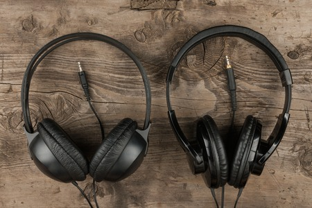 Two headphones and the cord symbolic of a love for music on an antique wooden texture background, top view