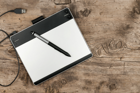 stylus: Graphics tablet with stylus lying on a wooden surface, top view with space for your text