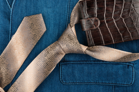 deep blue: Male tie and wallet lying on denim suit. View from above
