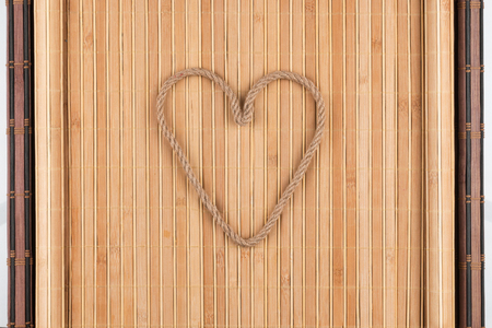 furled: Symbolic heart made of rope lying on a furled bamboo mat, as background, conceptual image