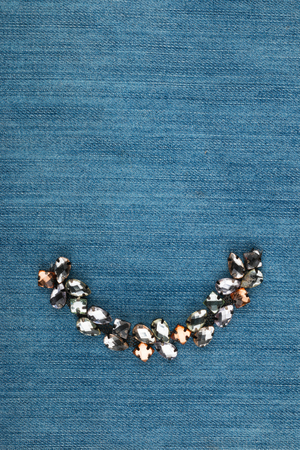 Fashionable background, jewelry with rhinestones lying on denim. View from above