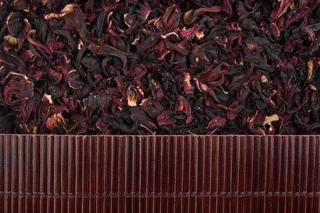 Beautiful bamboo mat on dry hibiscus as agricultural background. View from above