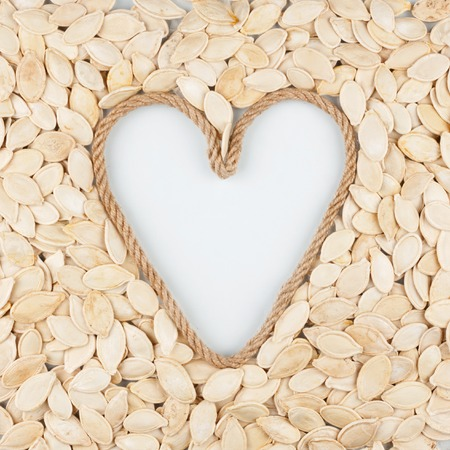 cordage: Pumpkin seeds and a rope in the shape of a heart with a place for designers. The concept of love of pumpkin