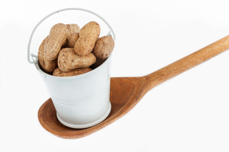 nutshells: Full bucket of peanut stands in a wooden spoon. The concept of food.