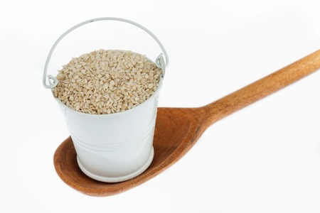 eating utensil: Full bucket of sesame grains stands in a wooden spoon. The concept of food. Stock Photo