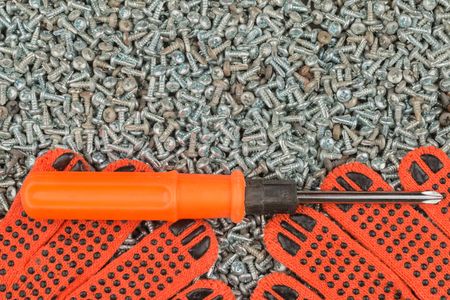 Screwdriver and work gloves lie on a pile of screws. Background, screen saver