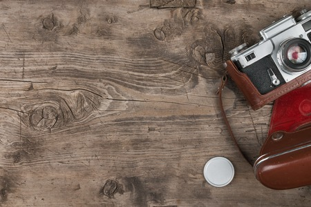 Retro camera in leather case on wooden background. View from above Stock Photo