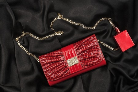 Bag of lacquered leather and red perfume lying on black silk. Handbag for women and bottle of scent, top view. Accessories in modern style. Fashion and glamour concept