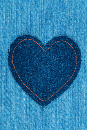Classic heart made of denim lies on a denim. Space for text. View from above