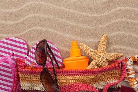 Beach bag with flip flops, sunglasses and sunscreen. Accessories for the beach. View from above