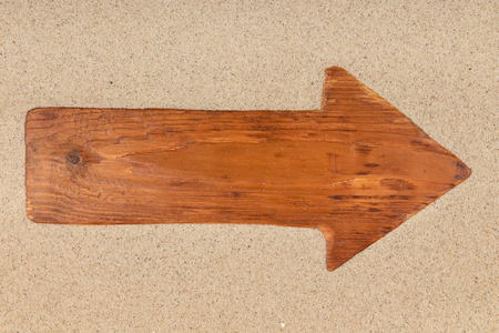 Arrow made from an old wooden board on the sand. View from above
