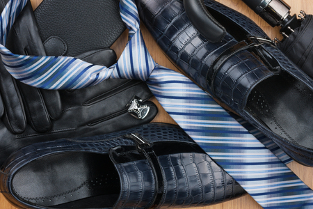 Classic men's shoes, tie, cufflinks, gloves, belt, purse on the wooden floor, can be used as background. Top view