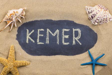 Handwritten word KEMER written in chalk, among seashells and starfishes. Top view