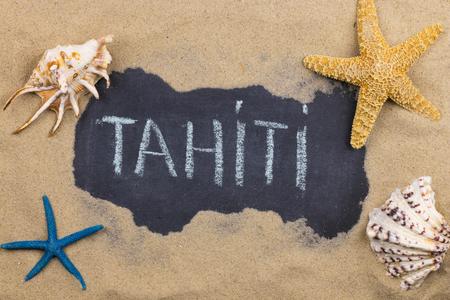 Handwritten word TAHITI written in chalk, among seashells and starfishes. Top view Imagens