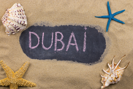 Handwritten word DUBAI written in chalk, among seashells and starfishes. Top view 版權商用圖片