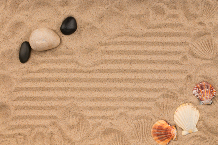 Stones, shells and their prints in the sand. Top view