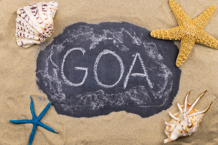 Handwritten word GOA written in chalk, among seashells and starfishes. Top view
