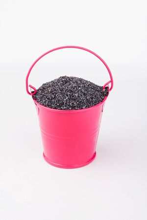Heap poppy grains in pink bucket on white background. Copy space