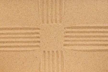 Texture of sand with lines in the form of a cross with a focus on the center. Top view. Copy space