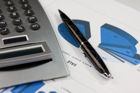 Financiële overzichten. Rekenmachine en pen op financiële grafieken. Detailopname. Bedrijfsconcept