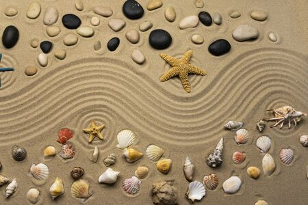 Stones, seashells and stars lie on the wavy lines of sand. View from above
