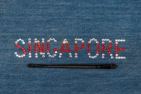 Inscription Singapore, inlaid rhinestones on denim. Top view. City of fashion, shopping, tourism.