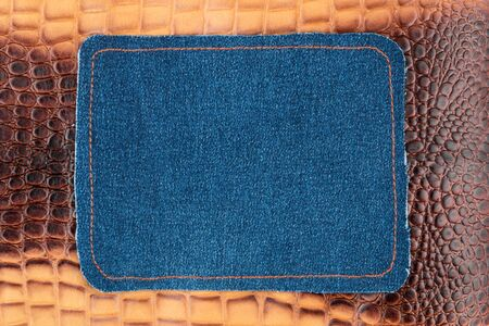 Blank jeans frame. Denim patch with orange thread seam on brown skin. With space for design, text place.