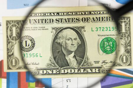 Close-up of one dollar through a magnifying glass. Business background. Money research concept. Top view