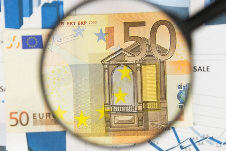 Close-up of fifty euros through a magnifying glass. Business background. Money research concept. Top view