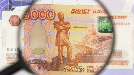 Close-up of five thousand rubles through a magnifying glass. Business background. Money research concept. Top view