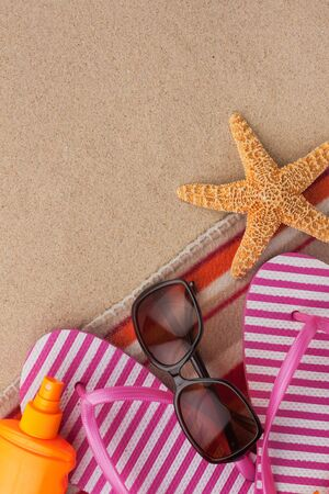 Summer accessories flip flops and towel. Sand beach texture background. With space for design, text place. Stock Photo