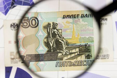 Close-up of fifty rubles through a magnifying glass. Business background. Money research concept. Top view