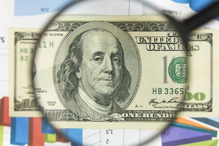 Close-up of hundred dollars through a magnifying glass. Business background. Money research concept. Top view