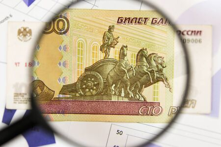 Close-up of hundred rubles through a magnifying glass. Business background. Money research concept. Top view